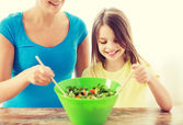 Little girl with mother mixing salad in kitchen — Stock Photo