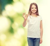 Kleine mädchen im weißen t-shirt, das ok geste — Stockfoto