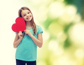 Smiling little girl with red heart — Stock Photo