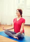 Smiling redhead teenager meditating at home — Stock Photo