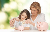 Mother and daughter putting money to piggy banks — 图库照片