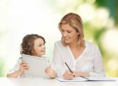 Woman with notebook and girl holding tablet pc — Stockfoto