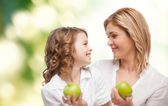 Happy mother and daughter with green apples — Stockfoto
