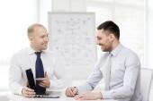 Zwei lächelnd geschäftsleute mit laptop im büro — Stockfoto