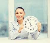 Attractive businesswoman with white clock — Stock Photo