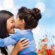 Happy little girl hugging and kissing her mother — Stock Photo #62453361
