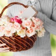 Man holding basket full of flowers and postcard — Stock Photo #62453417