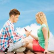 Couple with smartphones sitting on bench over sky — Stock Photo #62454113