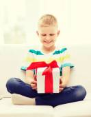 Smiling little holding gift box sitting on couch — Stock Photo