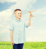 Smiling little boy holding a wooden airplane model — Stock Photo