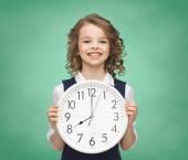 Smiling girl holding big clock — Stock Photo