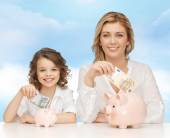 Mother and daughter putting money to piggy banks — Stock Photo