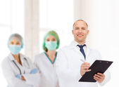 Smiling male doctor with clipboard — Stock Photo