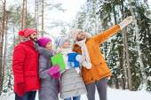 Smiling friends with tablet pc in winter forest — Fotografia Stock