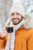 Smiling young man with cup in winter forest — Stock Photo