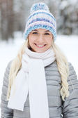 Smiling young woman in winter forest — Stockfoto