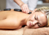 Close up of woman having hot stone massage in spa — ストック写真