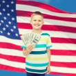Smiling boy holding dollar cash money in his hand — Stock Photo #62725249