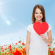 Smiling little girl with red heart — Stock Photo #62728113