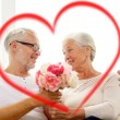 Happy senior couple with bunch of flowers at home — Stock Photo #62729935