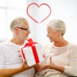 Happy senior couple with gift box at home — Stock Photo #62729971