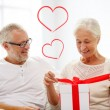 Happy senior couple with gift box at home — Stock fotografie #62729991