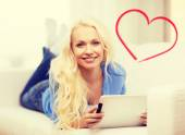 Smiling woman with tablet pc computer at home — Stock Photo