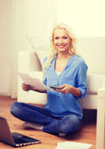 Smiling woman with papers, laptop and calculator — Stock Photo