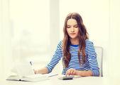 Chica estudiante con libro, calculadora y portátil — Foto de Stock