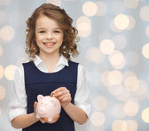 Smiling girl putting coin into piggy bank — Stock Photo