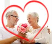 Happy senior couple with bunch of flowers at home — Stock Photo