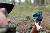 Close up of soldier or sniper with gun in forest — Stock Photo