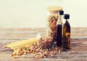 Close up of two olive oil bottles and pasta in jar — Stock Photo