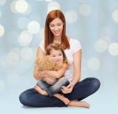 Happy mother with adorable girl and teddy bear — Stock Photo