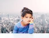 Sad little girl over city background — Stock Photo