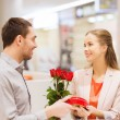 Happy couple with present and flowers in mall — Stock Photo #62813297