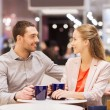 Happy couple with shopping bags drinking coffee — Stock Photo #62813357