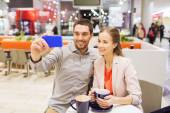 Happy couple with smartphone taking selfie in mall — Stock Photo