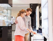 Happy couple choosing engagement ring in mall — Stock Photo