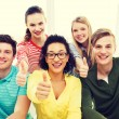 Smiling students at school showing thumbs up — Stock Photo #62997881