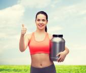 Teenage girl with jar of protein showing thumbs up — Stock Photo