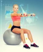 哑铃坐在健身球上的女人 — 图库照片