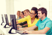 Smiling students in computer class at school — Stock Photo