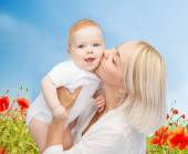 Happy mother with baby over natural background — Stock Photo