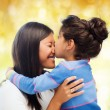 Happy little girl hugging and kissing her mother — Stock Photo #63003675