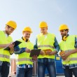 Group of smiling builders with tablet pc outdoors — Stock Photo #63006447