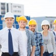 Group of smiling builders in hardhats outdoors — Stock Photo #63006695