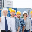 Group of smiling builders in hardhats outdoors — Stock Photo #63006723