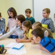 Group of kids with teacher and computer at school — Stock Photo #63007379