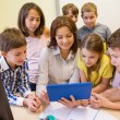 Group of kids with teacher and tablet pc at school — Stock Photo #63007441